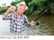 Купить «Fisherman changing bait on hook», фото № 32415450, снято 10 июня 2018 г. (c) Яков Филимонов / Фотобанк Лори