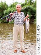 Купить «Fisherman posing with catch at riverside», фото № 32415470, снято 10 июня 2018 г. (c) Яков Филимонов / Фотобанк Лори