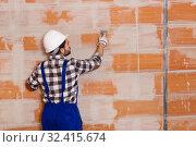 Купить «Workman is plastering the wall at the place», фото № 32415674, снято 6 марта 2019 г. (c) Яков Филимонов / Фотобанк Лори