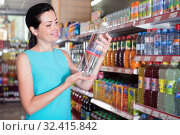 Купить «Portrait of adult female buying water in bottle», фото № 32415842, снято 6 июня 2017 г. (c) Яков Филимонов / Фотобанк Лори