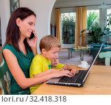 Eine junge Frau arbeitet zu Hause im Heimbüro und hat ein Kind an ihrer Seite. Стоковое фото, фотограф Zoonar.com/Erwin Wodicka / age Fotostock / Фотобанк Лори