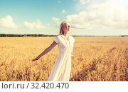 Купить «smiling young woman in white dress on cereal field», фото № 32420470, снято 31 июля 2016 г. (c) Syda Productions / Фотобанк Лори
