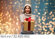 young woman in knitted winter hat holding gift box. Стоковое фото, фотограф Syda Productions / Фотобанк Лори