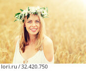 Купить «happy young woman in flower wreath on cereal field», фото № 32420750, снято 31 июля 2016 г. (c) Syda Productions / Фотобанк Лори
