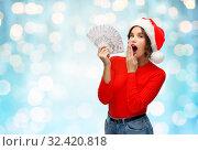 Купить «surprised woman in santa hat with money», фото № 32420818, снято 30 сентября 2019 г. (c) Syda Productions / Фотобанк Лори