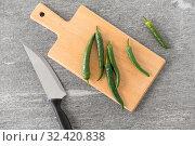 Купить «green chili peppers and knife on cutting board», фото № 32420838, снято 12 апреля 2018 г. (c) Syda Productions / Фотобанк Лори