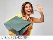 Купить «happy smiling young woman with shopping bags», фото № 32420894, снято 30 сентября 2019 г. (c) Syda Productions / Фотобанк Лори