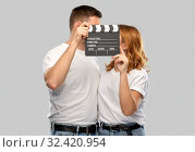 Купить «happy couple in white t-shirts with clapperboard», фото № 32420954, снято 6 октября 2019 г. (c) Syda Productions / Фотобанк Лори