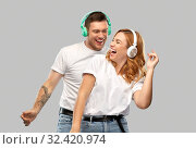 Купить «happy couple in headphones dancing», фото № 32420974, снято 6 октября 2019 г. (c) Syda Productions / Фотобанк Лори