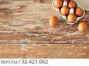 Купить «close up of eggs in cardboard box on wooden table», фото № 32421062, снято 16 августа 2018 г. (c) Syda Productions / Фотобанк Лори