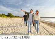 Купить «happy friends walking along summer beach», фото № 32421098, снято 31 августа 2019 г. (c) Syda Productions / Фотобанк Лори