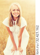 Купить «smiling young woman in white dress on cereal field», фото № 32421162, снято 31 июля 2016 г. (c) Syda Productions / Фотобанк Лори