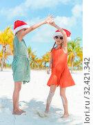 Купить «Little adorable girls in Santa hats during beach vacation have fun together», фото № 32421342, снято 5 апреля 2017 г. (c) Дмитрий Травников / Фотобанк Лори