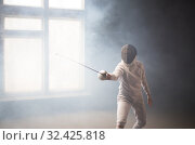 Купить «A young woman fencer standing in the attack position», фото № 32425818, снято 4 ноября 2019 г. (c) Константин Шишкин / Фотобанк Лори