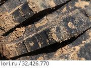 Купить «Close-up of old used rubber mud terrain tire with worn wear-resistant tread. Black muddy off-road tire on four-wheel drive truck», фото № 32426770, снято 12 сентября 2019 г. (c) А. А. Пирагис / Фотобанк Лори