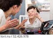 Cheerful boy telling story to mother. Стоковое фото, фотограф Яков Филимонов / Фотобанк Лори