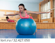 Cheerful female in fitness club having aerobic exercises with Swiss ball. Стоковое фото, фотограф Яков Филимонов / Фотобанк Лори