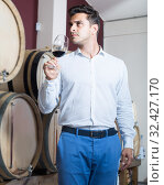 Купить «Cheerful male expert holding glass of red wine in shop», фото № 32427170, снято 13 декабря 2019 г. (c) Яков Филимонов / Фотобанк Лори