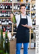 Купить «seller in apron holding bottle of wine», фото № 32427182, снято 6 июня 2020 г. (c) Яков Филимонов / Фотобанк Лори