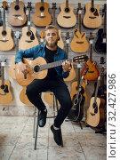Купить «Guitarist plays on acoustic guitar in music store», фото № 32427986, снято 11 сентября 2019 г. (c) Tryapitsyn Sergiy / Фотобанк Лори