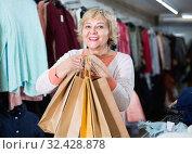 Купить «Woman consumer in the dress boutique among clothes with paper bags», фото № 32428878, снято 20 декабря 2017 г. (c) Яков Филимонов / Фотобанк Лори