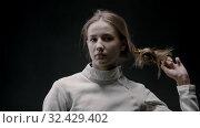 Купить «A young woman fencer lets her hair down», видеоролик № 32429402, снято 1 апреля 2020 г. (c) Константин Шишкин / Фотобанк Лори