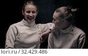 Купить «Two young smiling women fencers standing in the studio and looking in the camera», видеоролик № 32429486, снято 21 февраля 2020 г. (c) Константин Шишкин / Фотобанк Лори