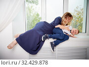 Beautiful elegant pregnant woman with blonde curly hair with small boy in the room. Mother having fun with young son in living room. Maternity concept. Стоковое фото, фотограф Кривошеина Елена Леонидовна / Фотобанк Лори