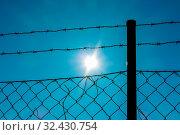 Stacheldraht und Sonnenschein, Symbol für Gefangenschaft, Grenze, Freiheit. Стоковое фото, фотограф Zoonar.com/Erwin Wodicka / age Fotostock / Фотобанк Лори
