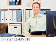Geschäftsmann sitzt am Schreibtisch mit Computer und einer Akte in der Hand. Стоковое фото, фотограф Zoonar.com/Robert Kneschke / age Fotostock / Фотобанк Лори