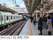 Train bound for Shinagawa and Tokyo arrive to station. Passengers wait the train on platform. It is the JR Yamanote Line most important train line in Tokyo city. Токио, Япония (2013 год). Редакционное фото, фотограф Кекяляйнен Андрей / Фотобанк Лори