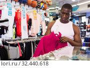 Купить «n man choosing tracksuit», фото № 32440618, снято 26 сентября 2019 г. (c) Яков Филимонов / Фотобанк Лори