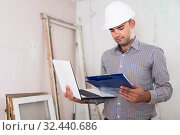 Купить «Portrait of attractive architect working at the notebook in helmet with documents», фото № 32440686, снято 18 мая 2017 г. (c) Яков Филимонов / Фотобанк Лори