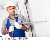 Купить «Adult male constructor renovating with drill in gloves», фото № 32440690, снято 18 мая 2017 г. (c) Яков Филимонов / Фотобанк Лори