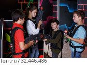Jolly teens aiming laser guns at other players. Стоковое фото, фотограф Яков Филимонов / Фотобанк Лори