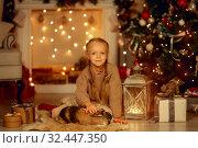 Купить «Happy little girl with brown rabbit at Christmas eve», фото № 32447350, снято 6 ноября 2019 г. (c) Julia Shepeleva / Фотобанк Лори