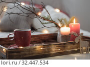 Red cup of tea on tray with burning candles on background sofa with pillows. Cozy home concept. Стоковое фото, фотограф Майя Крученкова / Фотобанк Лори