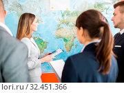 Geschäftsleute stehen vor einer Weltkarte und planen internationale Business Strategie. Стоковое фото, фотограф Zoonar.com/Robert Kneschke / age Fotostock / Фотобанк Лори