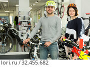 Купить «Smiling couple in helmet standing near bicycle», фото № 32455682, снято 8 января 2018 г. (c) Яков Филимонов / Фотобанк Лори