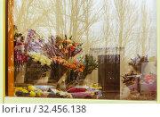 Торговый зал цветочного магазина, сфотографированный через окно с улицы. Отражения в стекле. Редакционное фото, фотограф Наталья Николаева / Фотобанк Лори