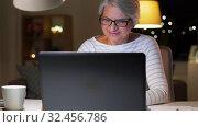 Купить «happy senior woman with laptop at home in evening», видеоролик № 32456786, снято 18 ноября 2019 г. (c) Syda Productions / Фотобанк Лори