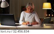 Купить «senior woman filling tax form at home in evening», видеоролик № 32456834, снято 18 ноября 2019 г. (c) Syda Productions / Фотобанк Лори