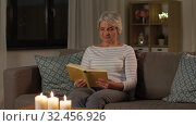 Купить «happy senior woman reading book at home in evening», видеоролик № 32456926, снято 18 ноября 2019 г. (c) Syda Productions / Фотобанк Лори