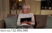Купить «happy senior woman with tablet pc at home at night», видеоролик № 32456986, снято 18 ноября 2019 г. (c) Syda Productions / Фотобанк Лори