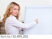 Geschäftsfrau zeigt mit ihrem Zeigefinger auf ein leeres Flipchart. Стоковое фото, фотограф Zoonar.com/Robert Kneschke / age Fotostock / Фотобанк Лори