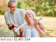 Alte Frau freut sich über das Geschenk zum Hochzeitstag im Garten. Стоковое фото, фотограф Zoonar.com/Robert Kneschke / age Fotostock / Фотобанк Лори