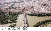 Купить «Aerial view of cityscape of Cordoba with Roman Bridge over the Guadalquivir and the Mosque-Cathedral of Cordoba», видеоролик № 32464690, снято 22 апреля 2019 г. (c) Яков Филимонов / Фотобанк Лори