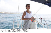 Купить «Young attractive woman standing at yacht wheel during luxury sea trip», видеоролик № 32464782, снято 30 июля 2019 г. (c) Яков Филимонов / Фотобанк Лори