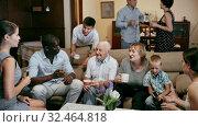 Купить «Big international family gathered together in parental home, cheerfully talking in living room», видеоролик № 32464818, снято 8 апреля 2020 г. (c) Яков Филимонов / Фотобанк Лори
