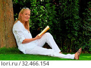 Eine junge Frau sitzt auf einer Wiese und liest ein Buch. Erholung im Park. Стоковое фото, фотограф Zoonar.com/Erwin Wodicka / age Fotostock / Фотобанк Лори